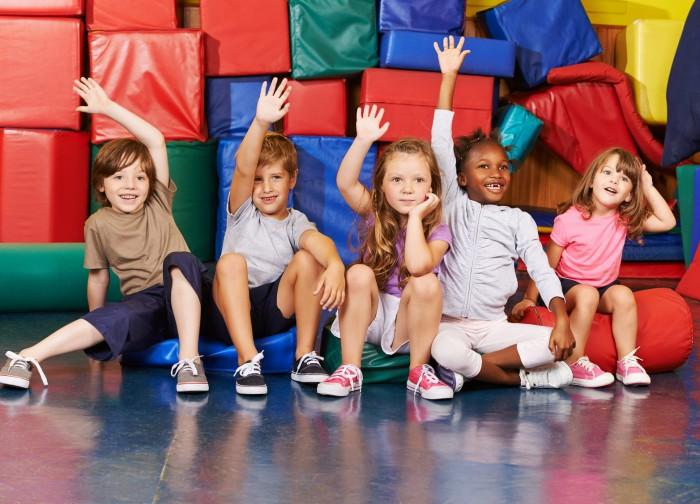 Glückliche Kinder heben Hände in der Turnhalle einer Grundschule