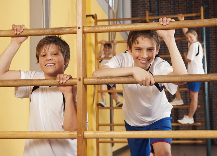 Germany, Emmering, Boys (12-14) climbing wall bars with girls in background